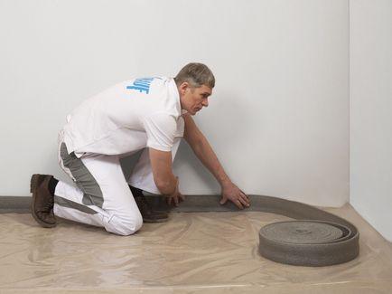 На разделительный слой по периметру помещения установите кромочную ленту. В углах, разрежьте ленту с помощью ножа. Это позволит исключить зазоры в местах примыкания.